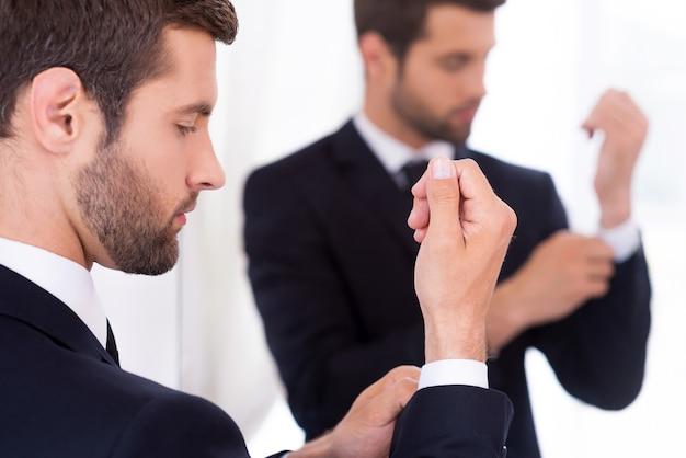 Регулировка рукавов. уверенный молодой человек в строгой одежде поправляет рукава, стоя у зеркала