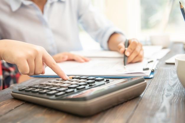 관리자 비즈니스 남자 재무 관리자 및 비서 보고서 만들기, 균형 계산.