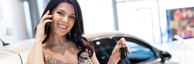 Admirable brunet speaking phone and posing near her new car in dealership showroom