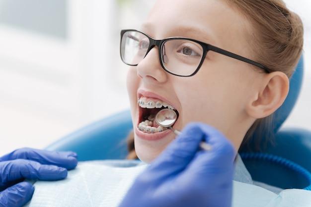 치과 의사의 의자에 앉아 치료가 필요한 동안 치아를 확인하는 훌륭한 영리한 헌신적 인 여성
