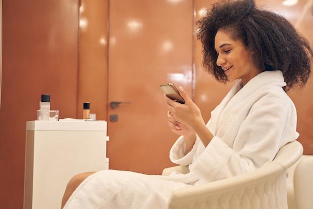 スパサロンの肘掛け椅子で休んでいる間、スマートフォンを持って好奇心を持ってメッセージをチェックしている立派な巻き毛の女性