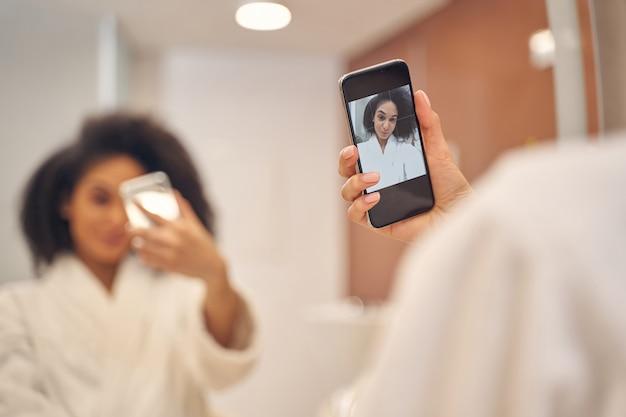 スマートフォンを持ってスパサロンでリラックスしながらセルフ写真を作る白いローブの立派な巻き毛の女性