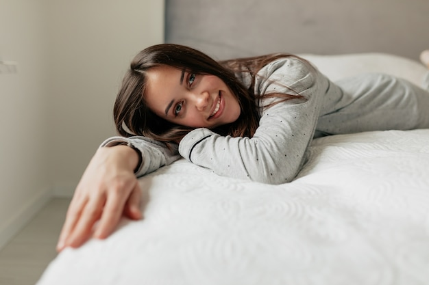 Admirable european woman in pajamas lying on the white bed and resting in good day at home.