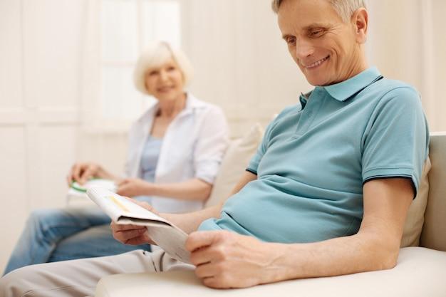 新聞を読んだりソファに座ったりしながら家で素敵な朝を楽しんでいる立派な知的な年配の男性