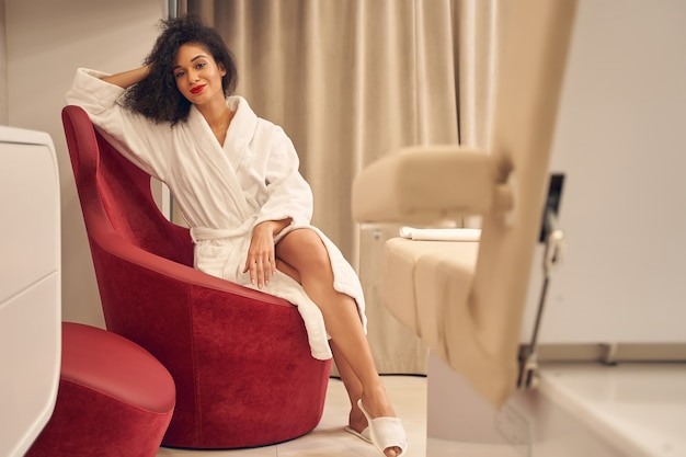 白いバスローブを着て、肘掛け椅子に座って足を組んでいる立派なポジティブな女性