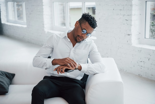 새로운 손목 시계를 존경합니다. 고전적인 마모와 안경에 세련된 아프리카 계 미국인 남자가 침대에 앉아있다