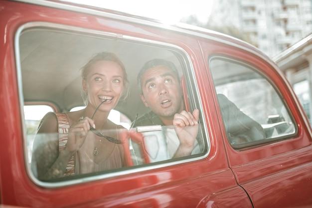 도시에 감탄. 빨간 복고차 창문 밖을 내다보는 관광객들, 미소를 지으며 안경을 깨물고 있는 여성, 입을 벌리고 있는 남성.