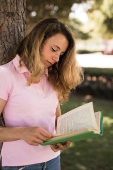 Adolescent female reading textbook in park