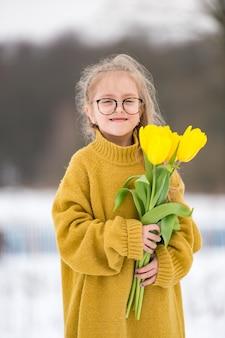 Маленькая девочка adorabe, одетая в большой взрослый свитер и сапоги отцов. красивая молодая девушка в очках, стоя на скамейке с букетом желтых тюльпанов в снежный зимний день.