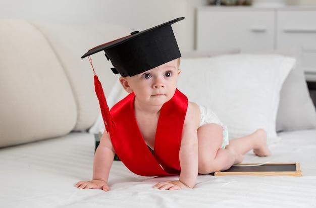 Очаровательный 10-месячный мальчик в выпускной кепке ползет