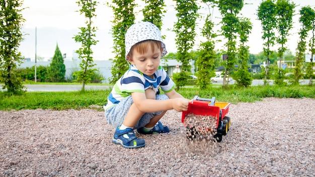 公園で砂とあなたのトラックとトレーラーで遊ぶ愛らしい 3 歳の幼児の少年