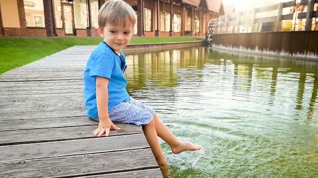 Adorable 3 years old toddler boy sitting on the riverbank in small european town at sunny summer day