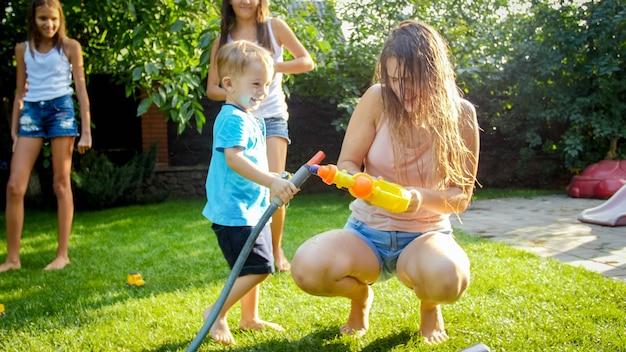 家の裏庭でプラスチックのおもちゃの銃から水をはねかける愛らしい3歳の幼児の男の子。夏に屋外で遊んで楽しんでいる子供たち