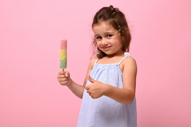 Прелестная 4-летняя девочка держит в руке здоровое веганское мороженое и показывает большой палец вверх, позирует на розовом фоне стены, копирует пространство. летний десерт, концепция веселого летнего настроения