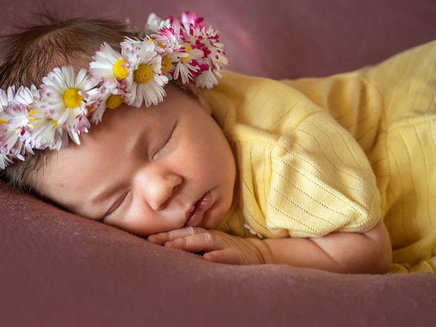 Adorable 8 days old newborn baby girl sleeping in daisy wreath yellow knitted dress on a soft plaid.