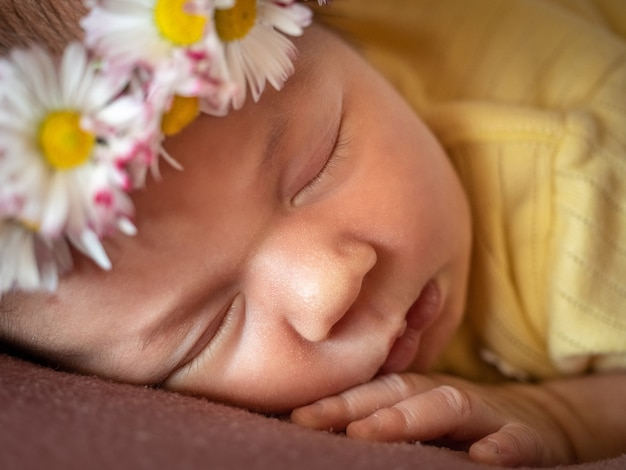 Adorable 8 days old newborn baby girl sleeping in daisy wreath yellow knitted dress on a soft plaid