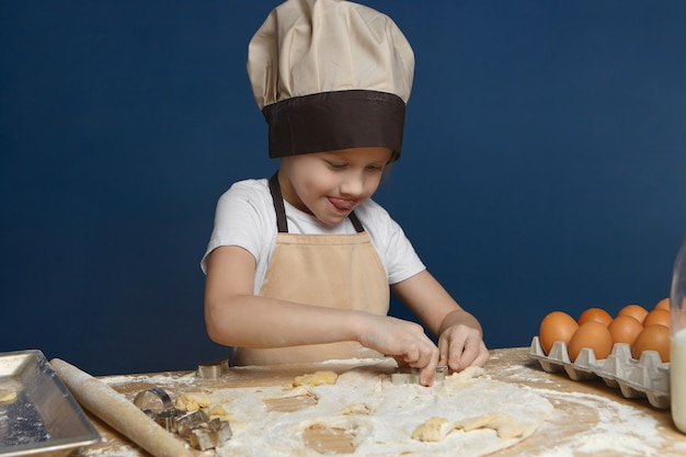 Adorable 8 year old male child in beige apron and hat standing in kitchen