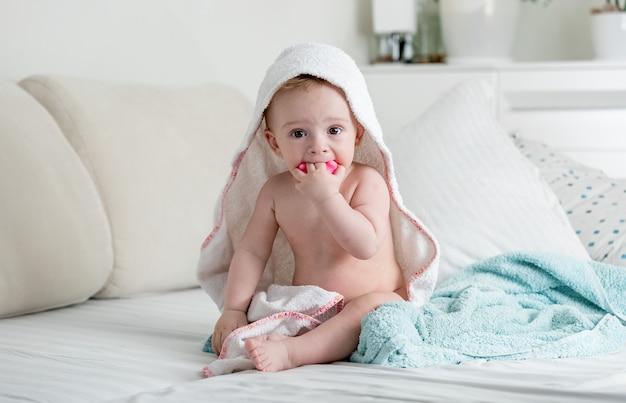 수건 아래 침대에 앉아 사랑스러운 9 개월 된 아기