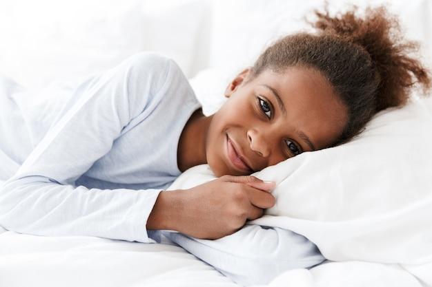 Очаровательная афроамериканская маленькая девочка улыбается и лежит в постели у себя дома