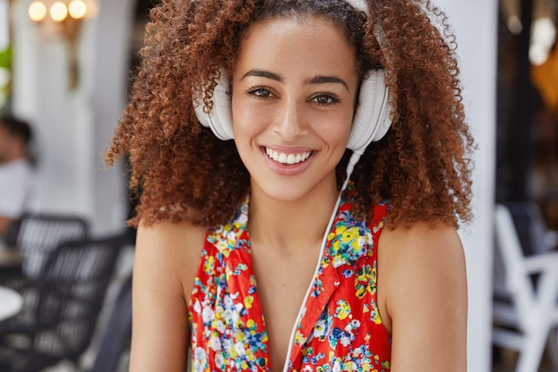 幸せな表情で愛らしいアフリカ系アメリカ人の女性は、明るいブラウスに身を包んだヘッドフォンで心地よい音楽を聞くのに満足し、幅広い笑顔を持っています。