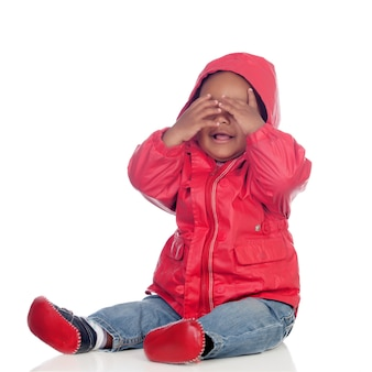 Adorable african baby sitting on the floor with red raincoat covering the face