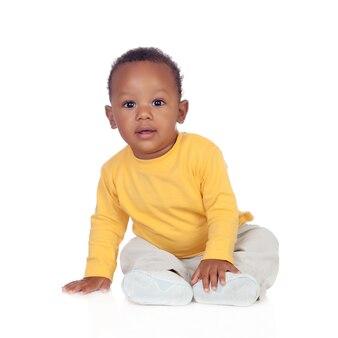 床に座って愛らしいアフリカの赤ちゃん
