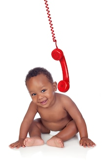 Adorable african baby with a vintage phone hanging down