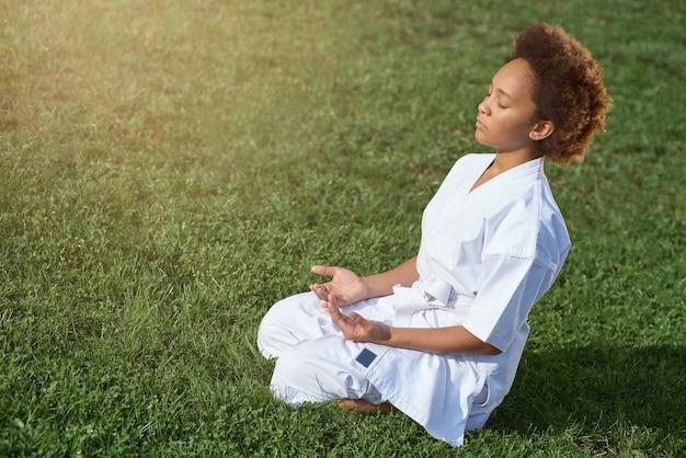 屋外で瞑想運動をしている愛らしいアフリカ系アメリカ人の女の子