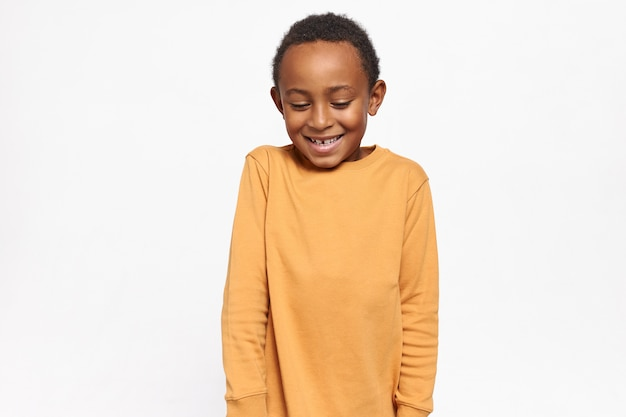 Adorable afro american kid in yellow sweater looking down shyly having timid facial expression