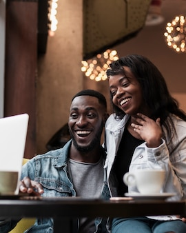 Adorable afroamerican couple looking at laptop