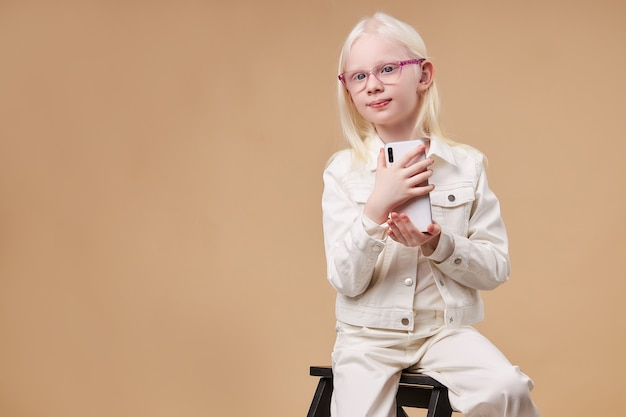 Adorable albino girl with charming appearance take photo on mobile phone