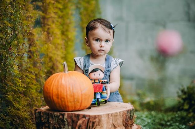 Очаровательная изумленная девочка со своей игрушкой, декоративными ножками и тыквой смотрит на кого-то