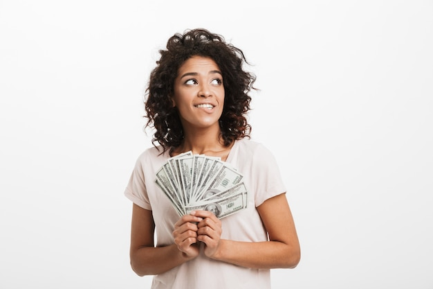 Adorable american woman with curly brown hair holding fan of money dollar banknotes and looking upward on copyspace, isolated over white wall