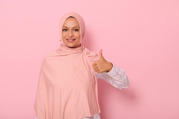 ヒジャーブの愛らしい魅力的なアラビア語の女性は、親指を立てて、コピースペースでピンクの背景の上に分離されたカメラを見て美しい歯を見せる笑顔で微笑む