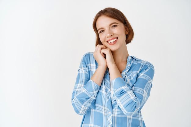 短い髪の愛らしい、かわいい若い女性は、顔に寄りかかって、魅了されて笑顔で、白い壁に立って、美しいものを賞賛します