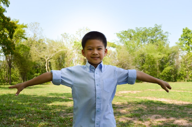 Adorable asian boy standing arms wide open.