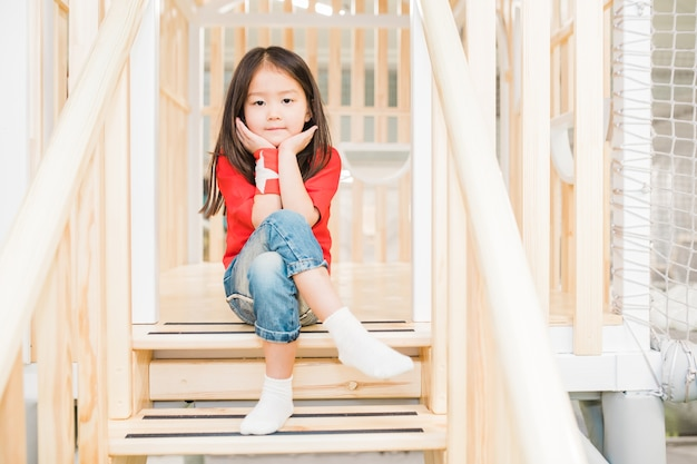 Adorable asian girl in casualwear sitting on wooden stairs at play area between railings and looking at you