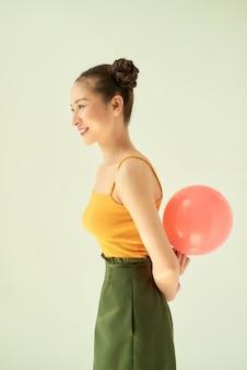 明るい背景に孤立して立っている間ピンクの風船を保持している愛らしいアジアの女の子。