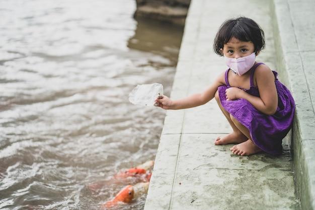 연못에서 잉어 잉어에게 먹이를 주는 건강한 얼굴 마스크를 쓴 사랑스러운 아시아 소녀