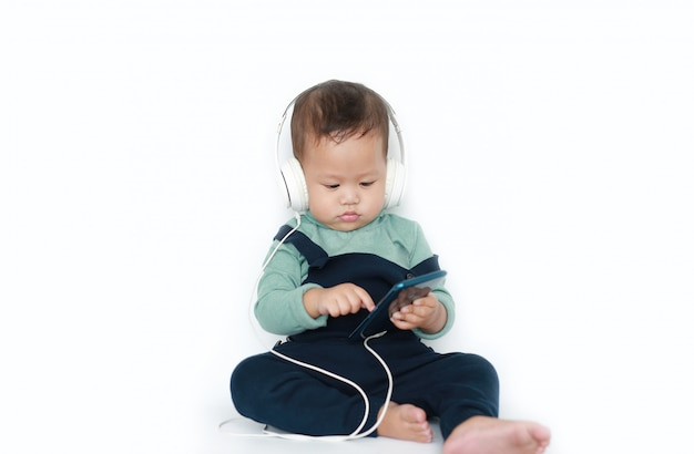 Adorable asian little baby boy enjoys listening music with headphones by smartphone