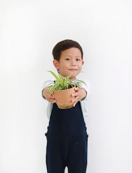 흰색 배경에 대해 나무 냄비를 주는 사랑스러운 아시아 소년. 그의 손에 있는 나무 냄비에 초점