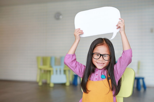 Adorable asian little girl holding empty blank speech bubble