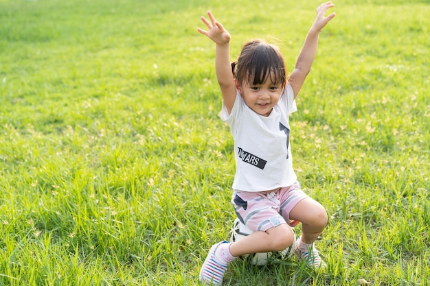 Adorable asian little girl is sitting on the football in the green field