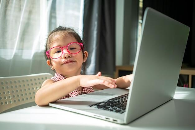 Очаровательная азиатская маленькая девочка печатает на портативном компьютере в гостиной дома