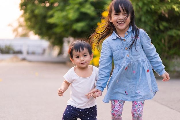 Adorable asian little toddler boy is holding hand with his big sister while he try to practice for first step