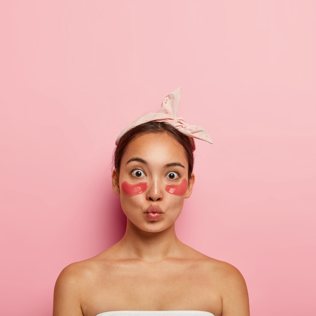 Adorable asian woman applies self sticking patches under eyes to reduce puffiness and dark circles, wears headband on head, keeps lips folded, stands bare shoulders, isolated on pink wall