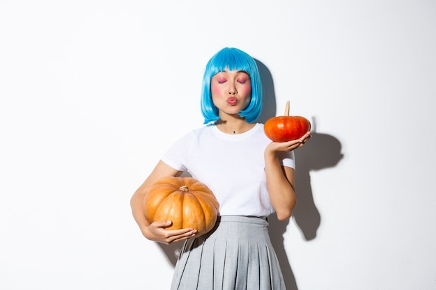 Adorable asian woman holding two pumpkins while kissing someone with closed eyes, celebrating halloween in blue wig and schoolgirl costume.