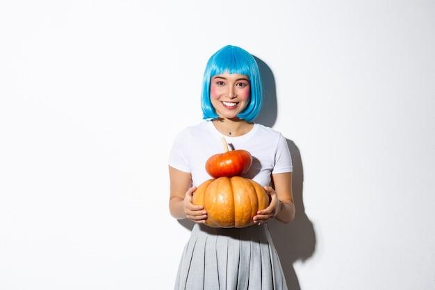 두 개의 귀여운 호박을 들고 카메라에 웃 고, 할로윈 파티를위한여 학생 옷을 입고 파란색가 발에 사랑스러운 아시아 여자.