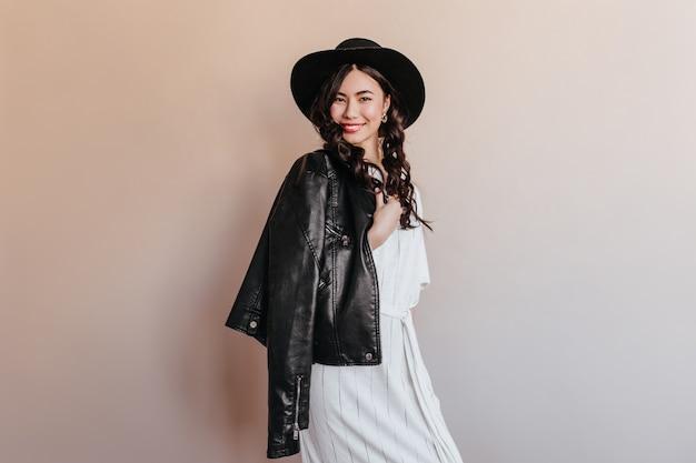 革のジャケットでポーズをとる愛らしいアジアの女性。ベージュの背景に立って笑っている韓国人女性のスタジオショット。