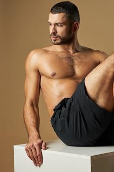 Очаровательный человек-спортсмен в черной спортивной одежде, глядя в сторону, отдыхая, изолированные на желтом фоне